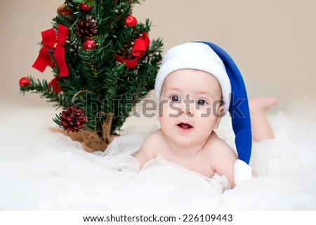 christmas cute baby boy/girl lying on white like on snowdrift, beautiful funny infant in Santa's hat - stock photo