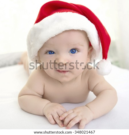 christmas cute baby boy or girl lying on white soft plaid like on snowdrift, beautiful funny infant in Santa's hat - stock photo