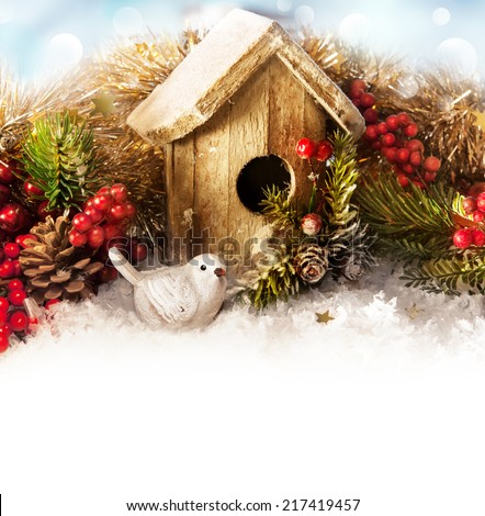 Christmas decor with Christmas tree and bird house on a snow background - stock photo