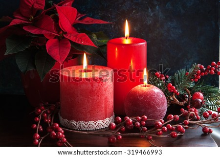 Christmas decor with red candles and poinsettia - stock photo