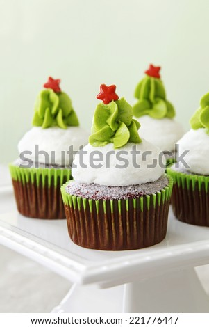 Christmas decorated red velvet cupcakes on a cakestand - stock photo