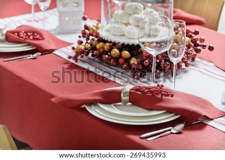 Christmas decorated table for the holidays with a candle and marshmallows, Christmas tree and red tablecloth - stock photo