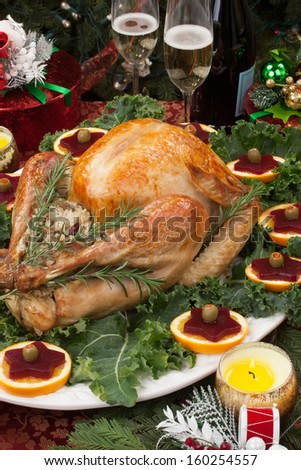 Christmas-decorated table with feast, gifts, roasted turkey, candles, champagne, and Christmas tree on back.  - stock photo