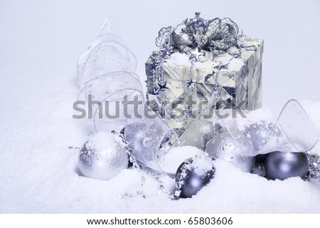 Christmas decoration and present covered with snow - stock photo