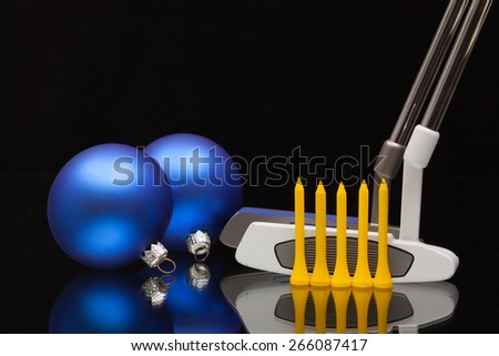 Christmas decoration and two golf putters  on a glass desk - stock photo