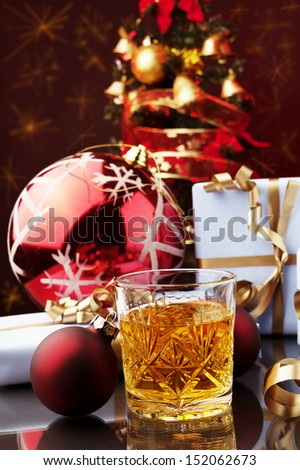 Christmas decoration and whiskey drink against color bakcground  - stock photo