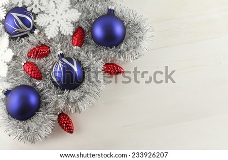 Christmas decoration - blue balls, red cones, white snowflakes, silver garland on white wooden background  - stock photo