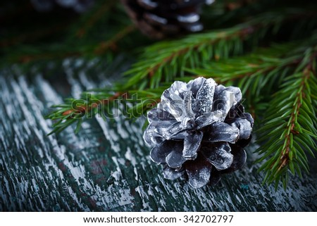 Christmas decoration card with  fir tree cone on rustic wooden background. Selective focus, shallow dof - stock photo