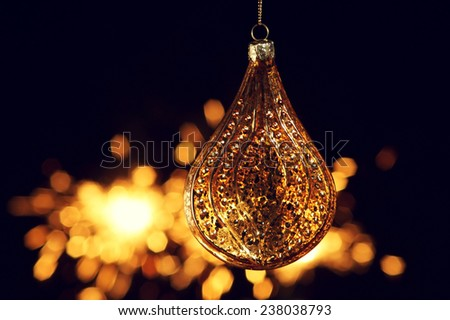 Christmas decoration. Close up of glass christmas ball against festive bokeh background. Warm golden colors of festive new year eve. - stock photo