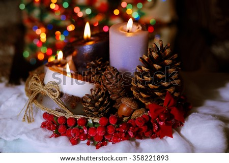 Christmas decoration closeup. Candles, fir cones. Eco still life. In the background are lit Christmas lights - stock photo