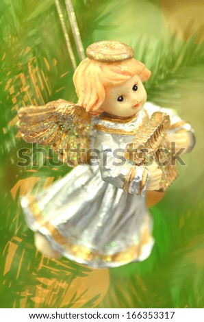 christmas decoration, figure of little angel playing the harp against bokeh background - stock photo