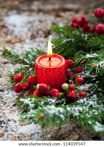 Christmas decoration: fir sprig,candle and berries in snow - stock photo