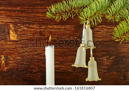 Christmas decoration. Fir-tree, bells and candle on wooden background. Selective focus - stock photo