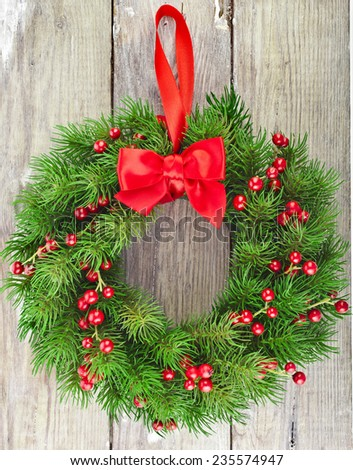 Christmas decoration fir wreath with red berries on wooden door sutface texture - stock photo