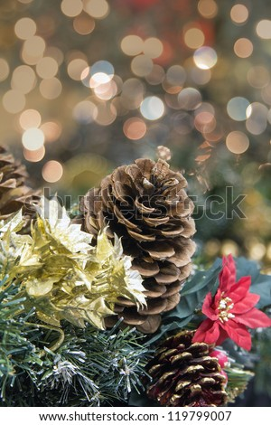 Christmas Decoration Garland with Poinsettia Pine Cones and Colorful Blurred Bokeh Lights Background - stock photo