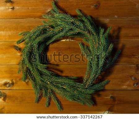christmas, decoration, holidays and advertisement concept - close up of natural green fir branch wreath on wooden board - stock photo