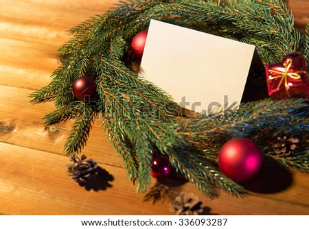 christmas, decoration, holidays, greeting and advertisement concept - close up of natural green fir branch wreath with white blank paper sheet and decorations on wooden board - stock photo