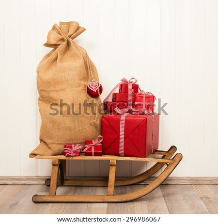 Christmas decoration in classical colors red and white with presents and an old sledge. - stock photo