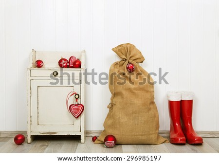 Christmas decoration in red and white colors with sack, presents and santa boots.. - stock photo