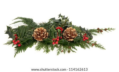 Christmas decoration of natural holly with red berry clusters and cedar leaf sprigs with gold pine cones over white background. - stock photo