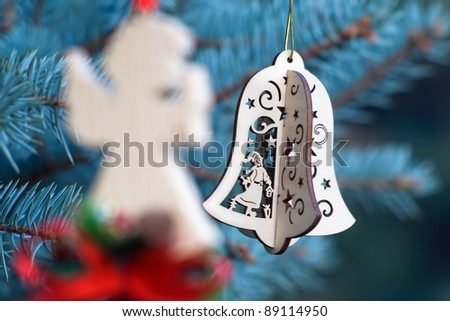 Christmas decoration of woody angel and handmade bell on the blue background of fir-tree - stock photo