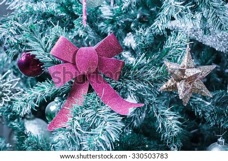 Christmas decoration on the fake snowy Christmas tree - stock photo