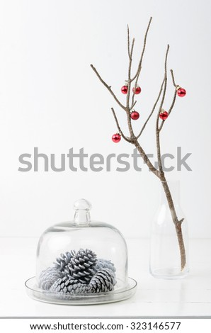 Christmas decoration ornaments, silver white pine cones in glass dome, bare branch in vase with red xmas baubles, plenty of copy space - stock photo