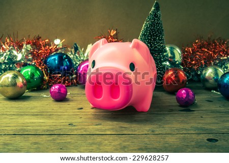 Christmas decoration, piggy  bank  on wooden background, abstract background to time to start to saving or solution for keep money for  celebration. - stock photo
