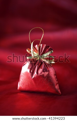 Christmas decoration (Red christmas sack) on a red silk background - stock photo