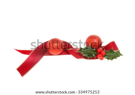 Christmas decoration, red ribbon and baubles with Holly isolated against white - stock photo