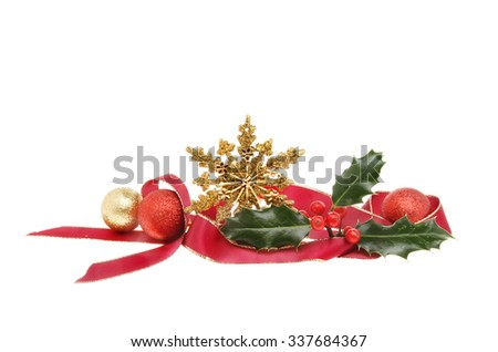 Christmas decoration, red ribbon, gold glitter star, baubles and Holly isolated against white - stock photo