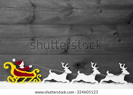 Christmas Decoration, Red Santa Claus With Yellow Sled And White Reindeer On Snow. Brown Vintage Wooden Background With Copy Space. Gray Christmas Card For Seasons Greetings. Black And White Image - stock photo