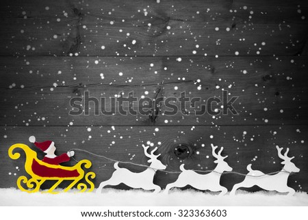 Christmas Decoration, Red Santa Claus With Yellow Sled And White Reindeer On Snow. Vintage Wooden Background With Copy Space. Gray Christmas Card For Seasons Greetings With Snowflakes. Black And White - stock photo