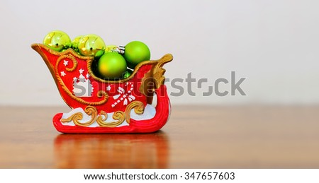 Christmas decoration - red sledge filled up with green christmas balls with place for your text. - stock photo