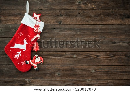 Christmas decoration stocking and toys hanging over rustic wooden background - stock photo