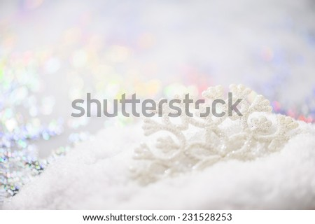 Christmas decoration - white snowflake on the snow with soft light blurred background, very shallow DOF. - stock photo