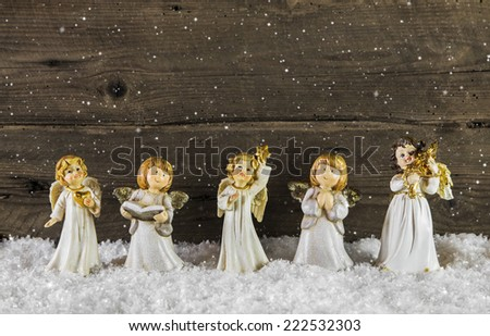 Christmas decoration with angels on wooden snowy background for a greeting card. - stock photo