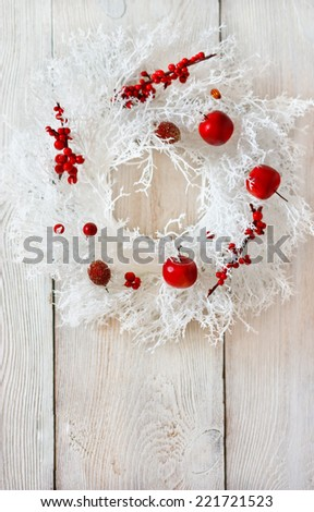 Christmas decoration with beautiful white Christmas wreath with red ornaments on a wooden board. - stock photo