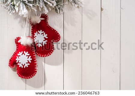 Christmas decoration with fir branches in the shape of mittens on wood background and place for text - stock photo
