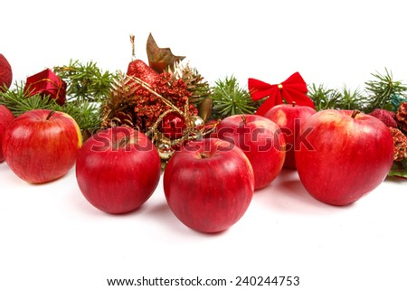 Christmas decoration with green pine or fir and many scattered red apples in middle. Holiday decorations isolated on white background. Empty or copy space for holiday greeting card - stock photo