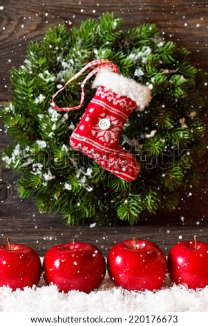 Christmas decoration with hanging wreath and stocking and ripe red apples on snow. - stock photo