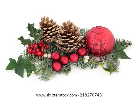 Christmas  decoration  with holly, red baubles, mistletoe, ivy, fir and cedar leaf sprigs with gold pine cones over white background. - stock photo