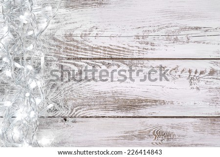 Christmas decoration with lights and white, wooden background - stock photo