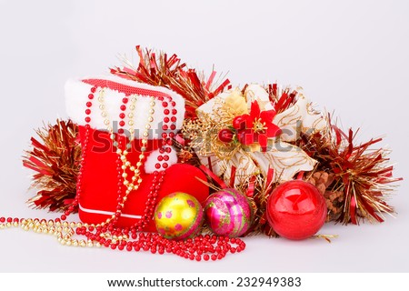 Christmas decoration with Santa's red boot, garland, balls, beads isolated on gray background. - stock photo
