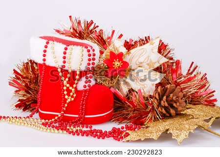Christmas decoration with Santa's red boot, garland, beads isolated on gray background. - stock photo
