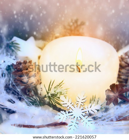 Christmas decoration with snowflake, candle and snow - stock photo