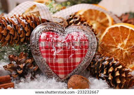 christmas decoration with vintage fabric heart,orange slices and cones on snow in rustic style - stock photo