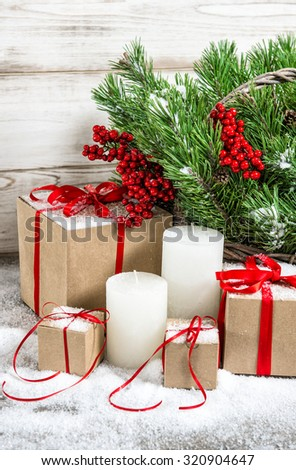 Christmas decoration with white candles and gift box. Christmas tree branches - stock photo
