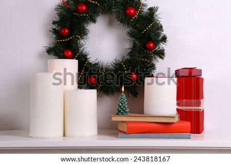 Christmas decoration with wreath and candles on shelf on white wall background - stock photo