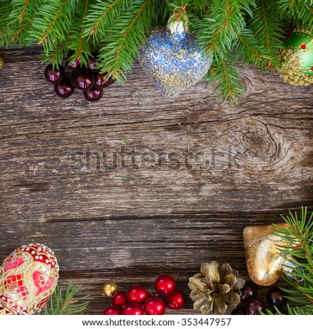 christmas decorations and fir tree frame on wooden background - stock photo